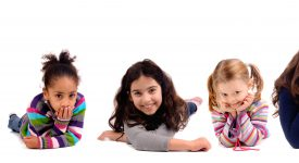 Children laying on white background smiling at camera photo