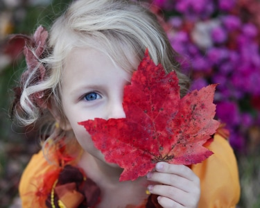 Girl with maple leaf covering one side of face photo