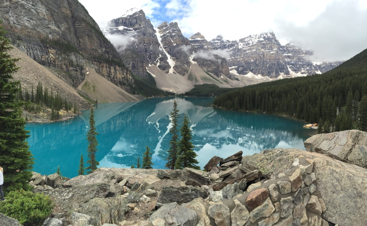 Photo of blue-green lake surrounded by snow-capped mountains