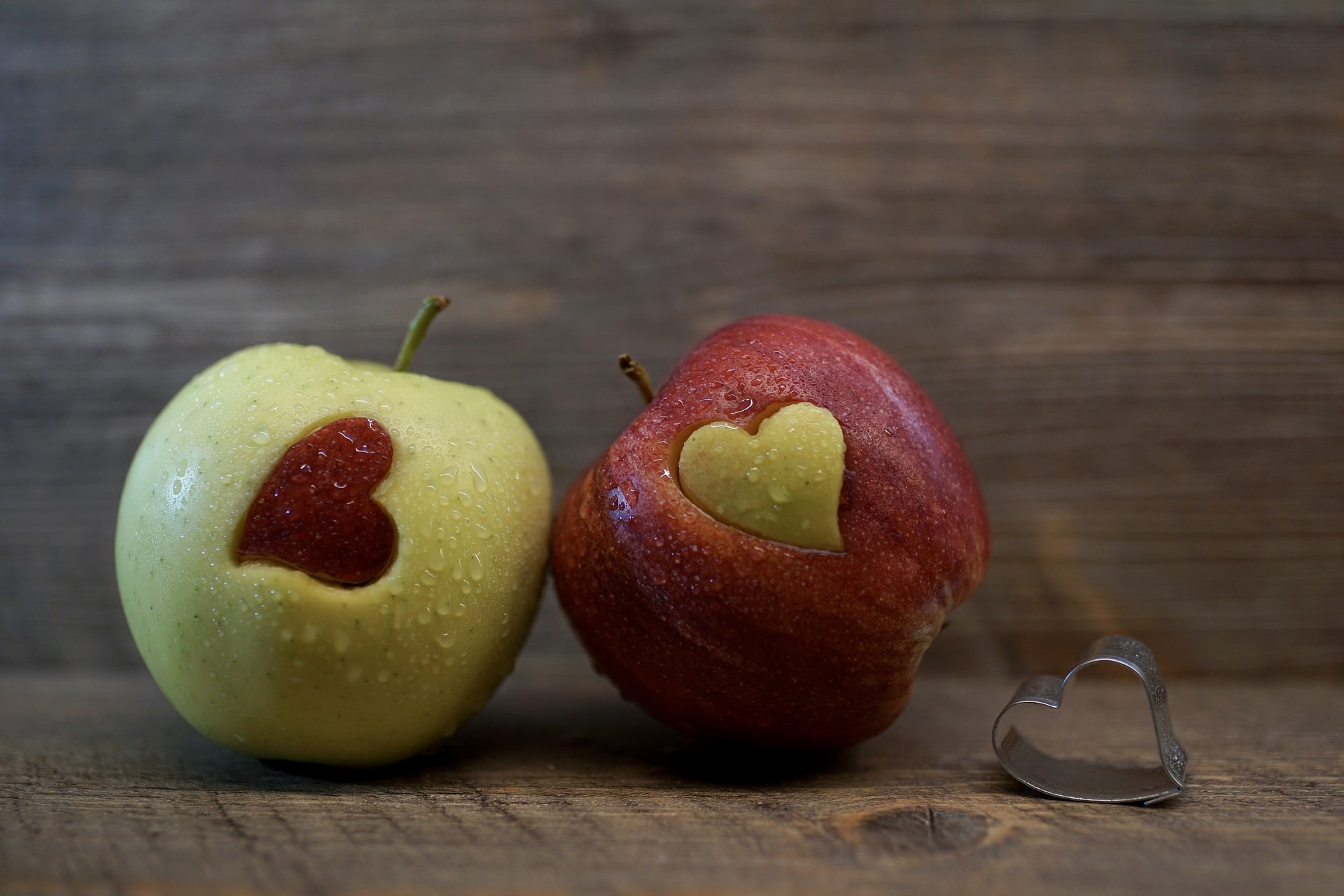 Photo of two apples with hearts cut out of them